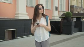 The lady tourist walks on the nice street, looks around and enjoys her trip. stock video