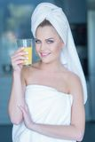 Lady in towel holding glass of juice Royalty Free Stock Images