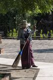 Woman cleaning with a straw broom, Bagan. Lady in traditional costume, cleaning a floor with a broom, outside of a temple in Bagan. Myanmar royalty free stock photography