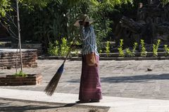 Woman cleaning with a straw broom, Bagan. Lady in traditional costume, cleaning a floor with a broom, outside of a temple in Bagan. Myanmar stock images