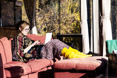 Lady in travel Style Outwear using Computer at Hotel Lobby. Adult Lady in travel Style colorful Clothing Poncho and yellow socks sitting on red Sofa and working Royalty Free Stock Photography