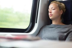 Lady traveling napping on a train. Royalty Free Stock Photo