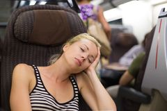 Lady traveling napping on a train. Royalty Free Stock Photography