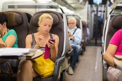 Lady traveling by train using smartphone. Royalty Free Stock Images
