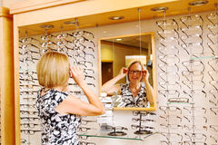 Lady trying on glasses. At optometry office Royalty Free Stock Photos