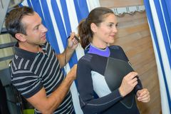 Lady trying on wetsuit. Lady trying on a wetsuit Royalty Free Stock Photography