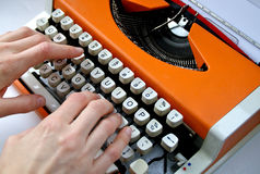 Lady typing orange vintage typewriter Royalty Free Stock Photography