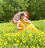 Lady with umbrella and yellow dandelions Stock Photo