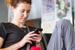 Lady using electronic device at airport terminal Stock Photo