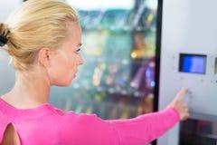Lady using a modern vending machine Royalty Free Stock Image