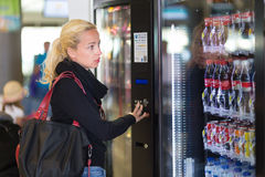 Lady using  a modern vending machine Royalty Free Stock Image