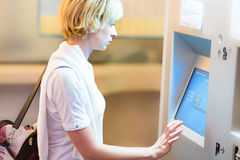 Lady using ticket vending machine. royalty free stock photo