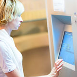 Lady using ticket vending machine. Royalty Free Stock Photography