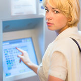 Lady using ticket vending machine. Royalty Free Stock Images