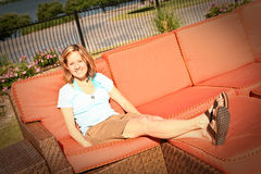 Lady on Vacation On Pool Area Couch Stock Image