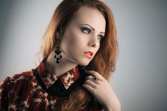 Lady vamp. Sensual fashion portrait of redhead vamp girl with long hair. Shallow depth of field Stock Image