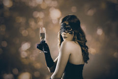 Lady with venetian mask and champagne. Beautiful woman with venetian carnival mask holding champagne glass and toasting. Lady at evening event party in front of Stock Photos