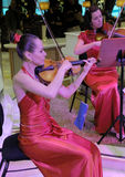 Lady Violinists. Play. Deep red dresses and moody magenta spotlighting on the subjects Stock Image