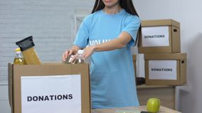 Lady volunteer packing food in cardboard boxes donations for low-budget families