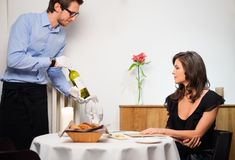 Lady and waiter in restaurant. Waiter offering wine to lady in restaurant royalty free stock images