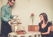 Lady and waiter in restaurant. Waiter offering wine to lady in restaurant stock image