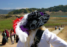 Lady in Waiting. At a Renaissance and pirate fair near Ojai, California, a woman in a festive hat surveys the scene royalty free stock photo