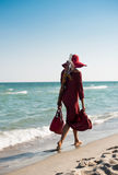 Lady walking along seashore Royalty Free Stock Photos