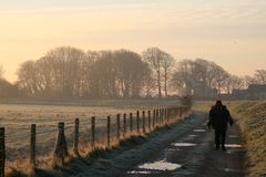 Walking on track soon after sunrise frosty morning. Lady walking along a track by a sea wall towards a group of trees on a frosty, winter morning soon after royalty free stock images