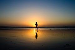 Lady walking on a beach. During sun set Stock Photos