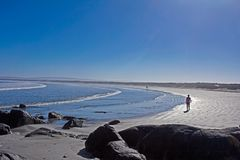 Lady walking on beach in morning. Lady walking along sparkling beach in early morning royalty free stock photos