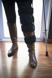 Lady walking on crutches in hospital clinic Stock Image