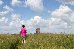 Lady walking in a field Royalty Free Stock Image