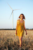 Lady walking in the field with windmill Royalty Free Stock Photo