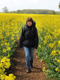 Lady walking between Fields of Yellow Rapeseed Royalty Free Stock Photo