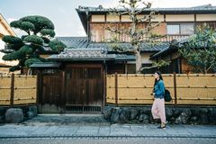 Lady walking by the Japanese traditional building. Full length photo of a pretty lady walking by the Japanese traditional building house. self-guided trip in royalty free stock images