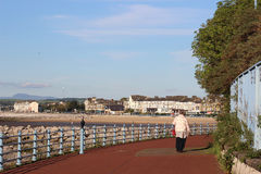Lady walking on promenade Morecambe, Lancashire. On a sunny, summer evening with the sands and buildings on the seafront, Marine Drive Central, in the royalty free stock photography