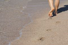 Lady walking on a sandy beach Stock Photos