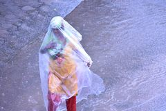 Lady walking on the streets on a rainy day. A lady covered herself with plastic sheet is walking on the streets during a rainy day in Mohali, India royalty free stock photo