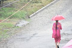 Lady walking with a umbrella in the rain royalty free stock photos