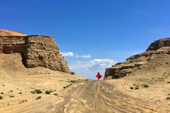 Tourist and Urho Ghost City, Xinjiang China. A lady is walking in Urho Gohost City. Yardang landforms in Xinjiang,China. Located 100 km northeast of Karamay Royalty Free Stock Photo