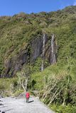 Lady walking on valley footpath, waterfall at side. Lady with walking pole on valley footpath through trees with waterfall cascading down the steep valley side stock images