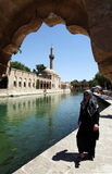 A lady walks next to Balikli GolAbrahams Pool in Urfa in Turkey. A lady walks next to Balikli Gol Abraham`s Pool in Urfa Sanliurfa. In the background stands the Royalty Free Stock Image