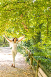 Lady walks with open arms in park Stock Photos