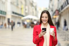 Lady walks in the street using a smart phone in winter. Front view portrait of a happy lady walking in the street using a smart phone in winter with copy space royalty free stock photo