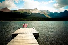 A lady was at a pier and opened her hands to greet the sky in Canada. In the distance, there are mountains, Columbia glaciers, lakes, trees and sunlight royalty free stock photos