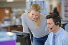 Lady watching over male colleague wearing headset and using computer royalty free stock images