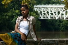 Lady by the water. African american lady by water an bridge royalty free stock images