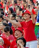 Lady waving Singapore flag during NDP 2009 Stock Photography