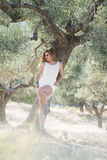 Lady wear white dress under the olive tree Stock Photography