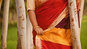 Lady standing wearing stylish saree unique photo. A lady wearing beautiful red saree standing in a place unique photo stock images